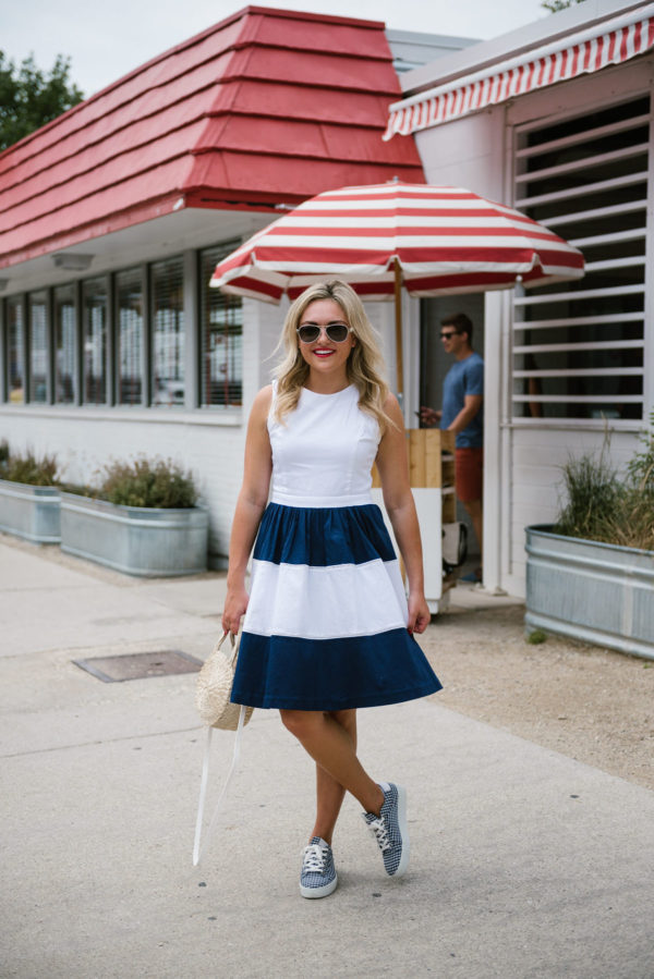 Fashion blogger Bows & Sequins wearing a navy striped dress with Coach aviators, a straw bag, and navy gingham sneakers in Chicago.