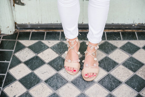 Fashion and lifestyle blogger Bows & Sequins wearing Loeffler Randall pom pom sandals with Old Navy white denim jeans.