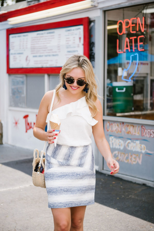 Jessica of Bows & Sequins, a fashion-focused lifestyle blog, wearing a white crop top with a blue striped mini skirt and a Clare V Petit Alice straw bag.