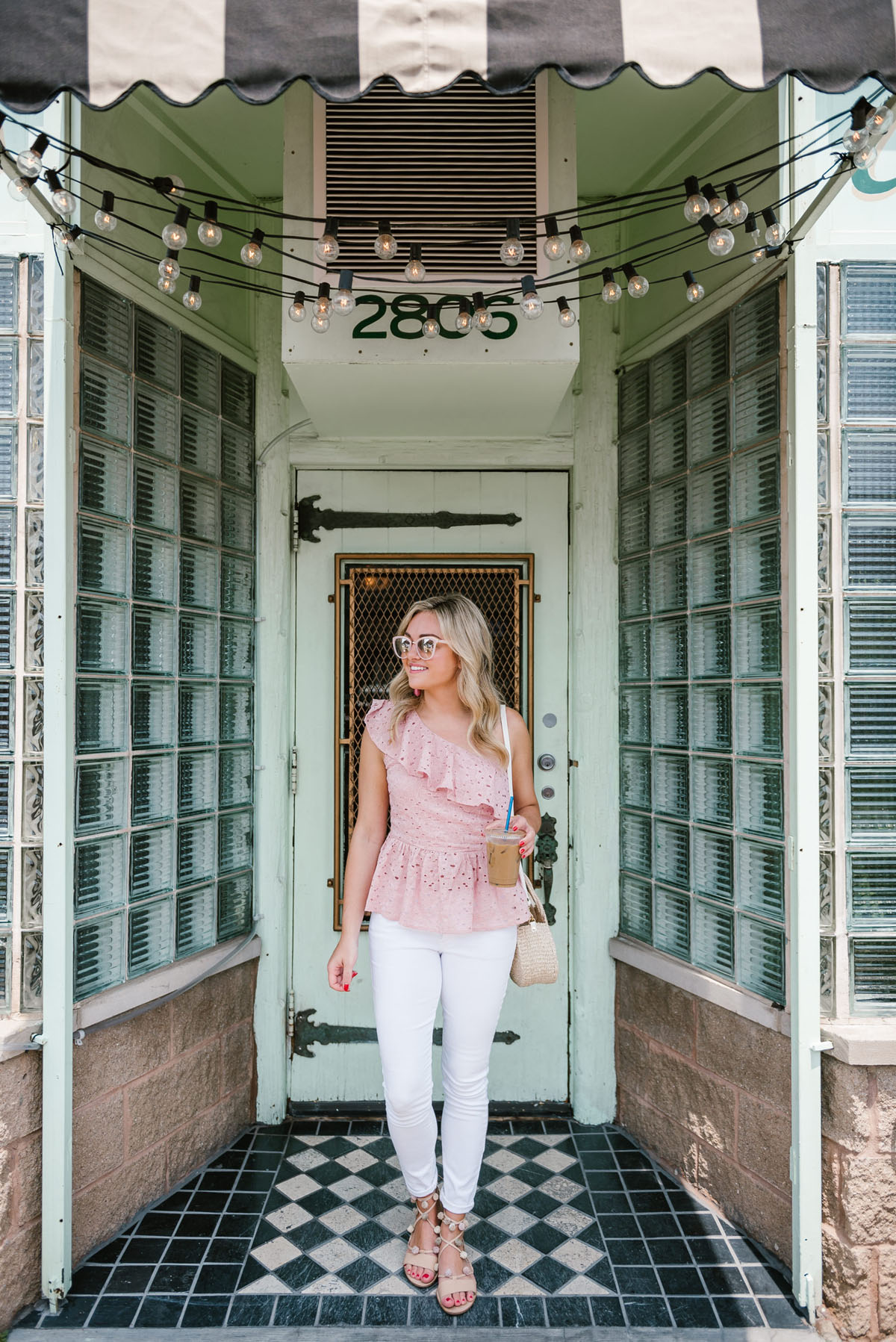 Bows & Sequins wearing a J.O.A. pink peplum top, Old Navy white denim, heeled pom pom sandals, and a Clare V straw crossbody bag.