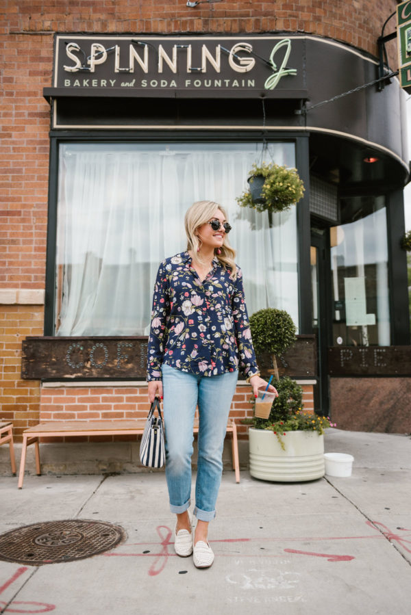 Chicago blogger Bows & Sequins outside the Spinning J coffee bar wearing a floral blouse from Nordstrom Rack, Vineyard Vines straight leg jeans, white leather loafers, and a Julie Vos cuff.