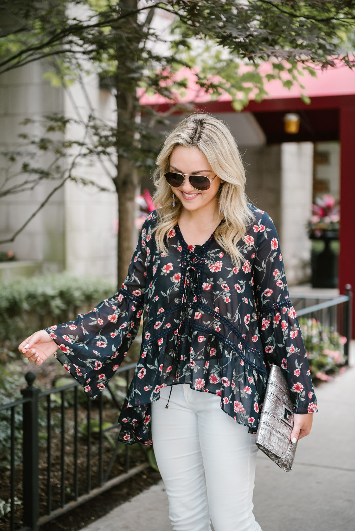 Bows & Sequins wearing a Moon River flare sleeve floral blouse with a metallic silver clutch and Gucci aviators.