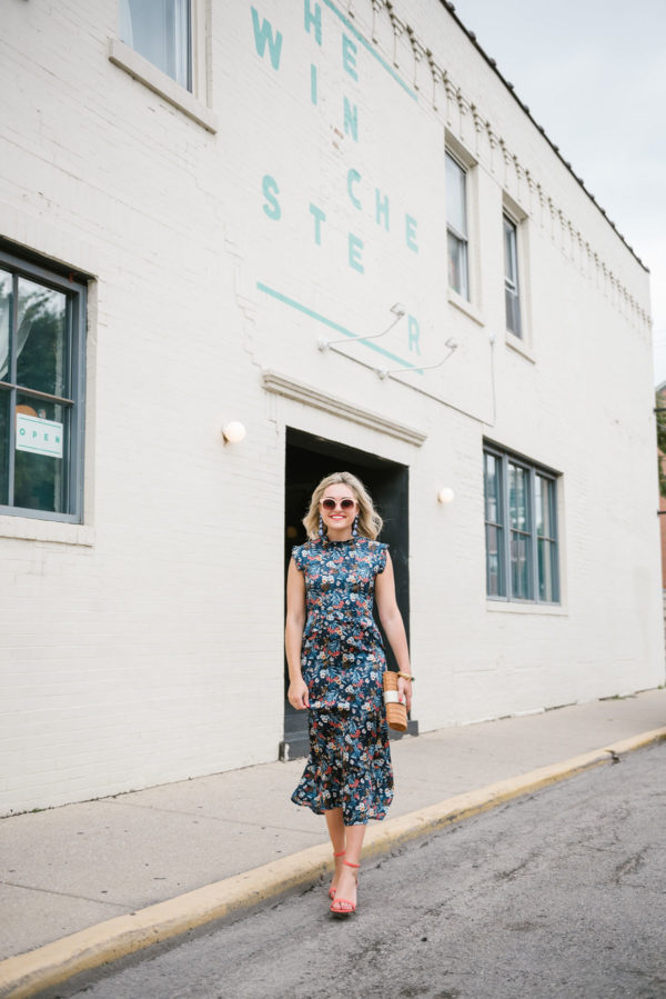 Chicago blogger Bows & Sequins wearing a floral midi dress outside the Winchester restaurant.