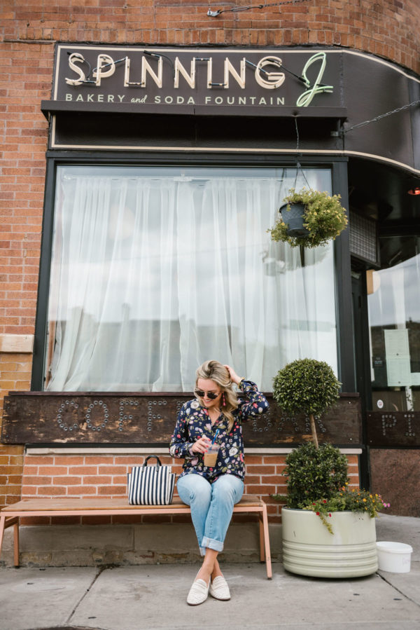 Bows & Sequins wearing a floral blouse, cuffed straight leg denim, and white leather loafers at a coffee shop in Chicago.