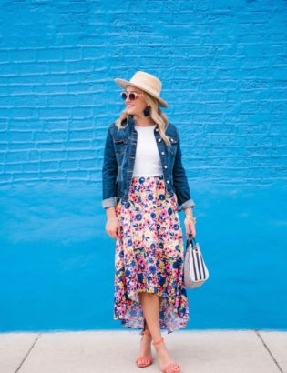 Chicago-based lifestyle blogger Bows & Sequins styling a high-low floral dress with coral sandals, a straw hat, and a dark denim jacket.