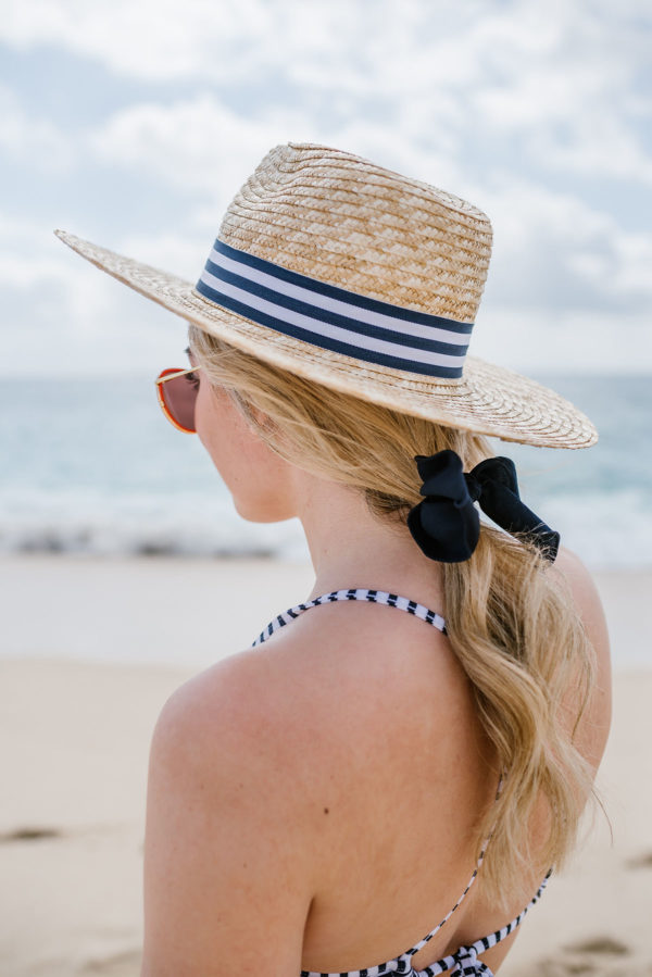 Bows & Sequins wearing a striped straw hat with a hair bow and a swimsuit on the beach.