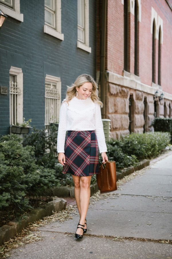 Chicago-based lifestyle blogger Bows & Sequins styling a plaid skirt for work with a Nat & Nin leather tote, J.Crew Mary Janes, and a white lace top.