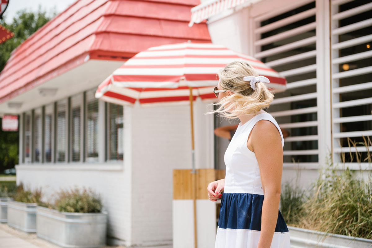 Jessica Sturdy, of the fashion and lifestyle blog Bows & Sequins, wearing a J.Crew white eyelet hair bow and an Elizabeth McKay navy striped dress.