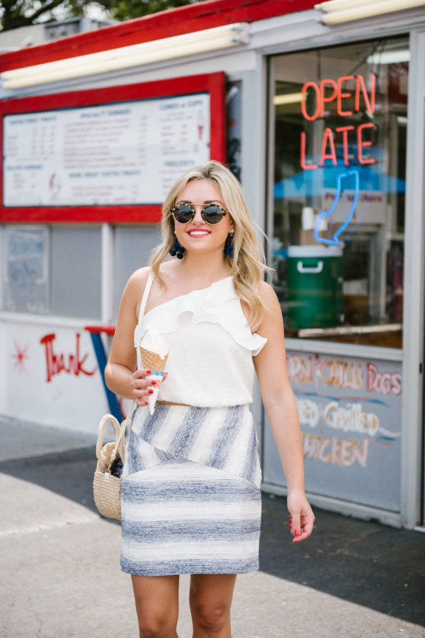 Jessica of Bows & Sequins styling a blue and white striped Hutch skirt from Anthropologie with a white ruffle crop top from Nordstrom, Illesteva sunglasses, and BaubleBar pom pom earrings.