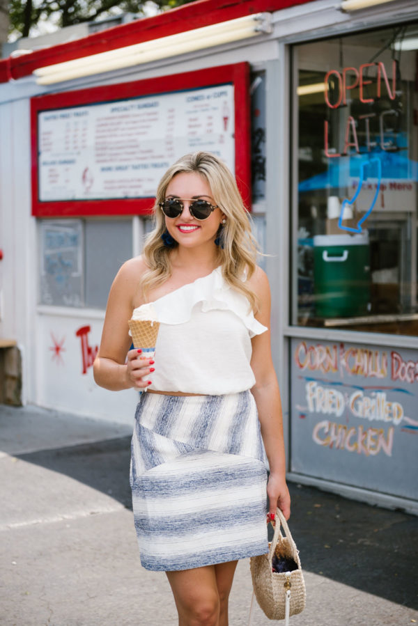 Bows & Sequins, a style and fashion blogger, wearing a blue and white striped mini skirt with a one shoulder ruffle crop top and a straw bag.