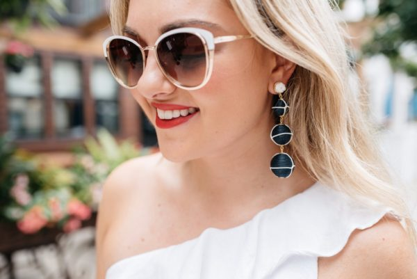 Chicago based fashion and lifestyle blogger, Bows & Sequins, wearing Call It Spring sunglasses and Baublebar navy and white nautical earrings with Dolce & Gabbana red lipstick.