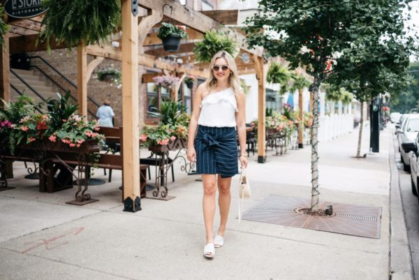 Bows & Sequins wearing a ruffle one-shoulder crop top and a navy pinstripe tie-front skirt with Call It Spring sunglasses and Kurt Geiger slides.