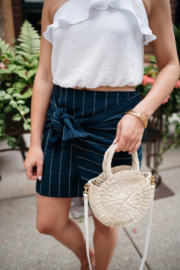 Bows & Sequins holding a Clare V straw tote and wearing a J.O.A. tie-front pinstripe skirt and a Chanel bracelet via Switch.