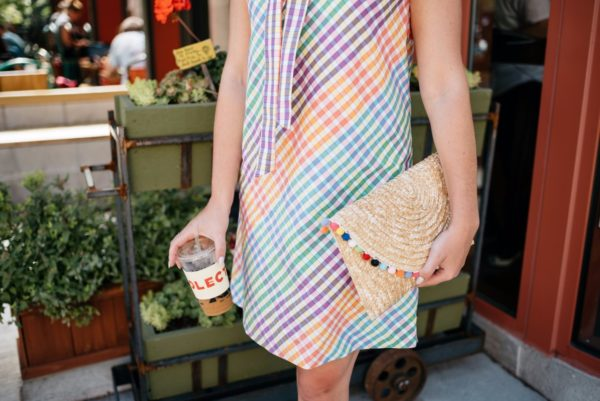 Bows & Sequins wearing a striped dress from J.Crew with a White Elephant Designs pom pom clutch.