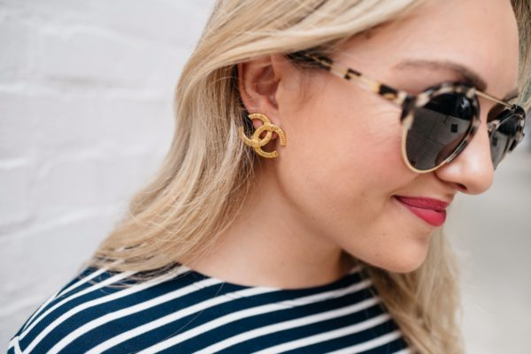 Chicago-based fashion and lifestyle blogger Bows & Sequins wearing gold Chanel earrings, Illesteva sunglasses, and Bare Minerals 'Juicy' matte lipstick.