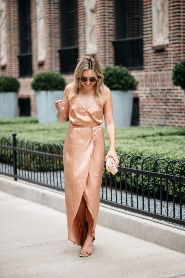 Chicago fashion and lifestyle blogger Bows & Sequins wearing a metallic wrap dress, gold rim aviators, camel wedges, and nude lipstick with a gold clutch.