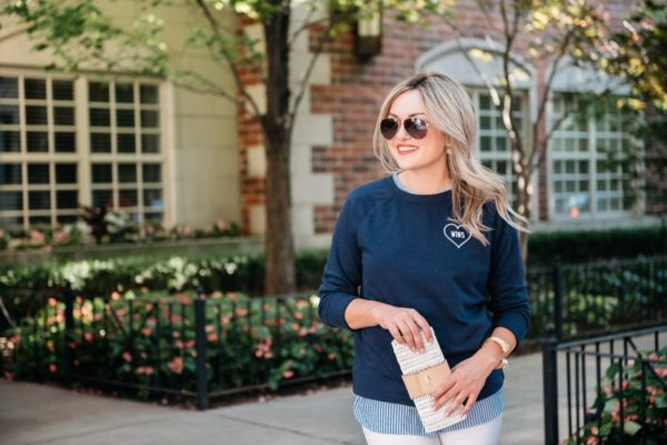 Bows & Sequins layering a chambray top with an Old Navy Love Wins graphic sweatshirt. Also wearing Gucci aviators, Vineyard Vines rattan wicker clutch and a Julie Vos gold cuff.