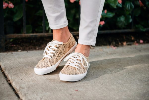 Bows & Sequins wearing Old Navy white denim jeans and leopard sneakers.