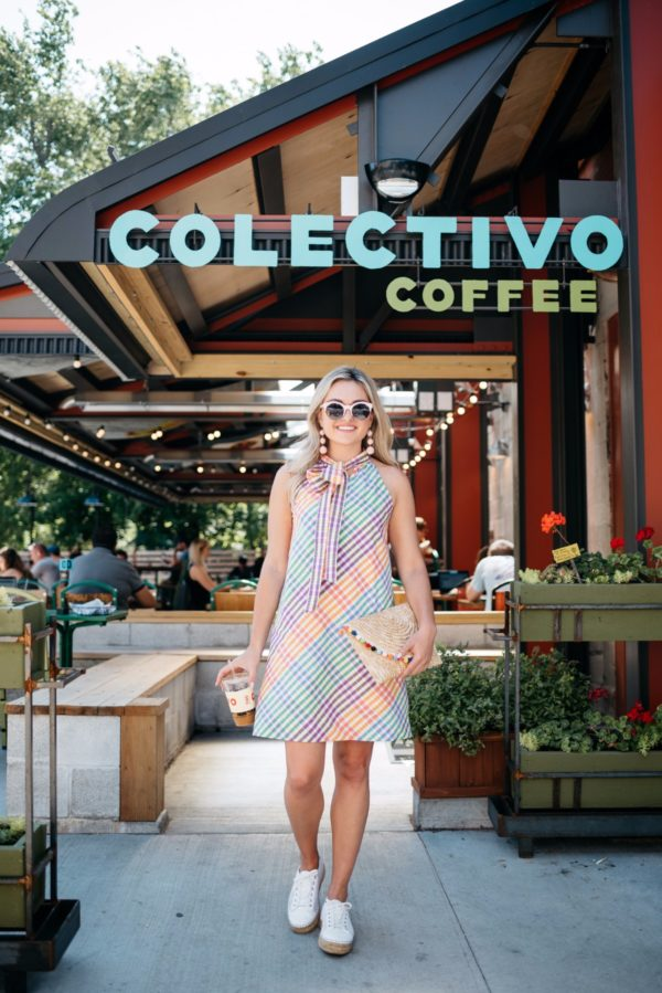 Chicago lifestyle blogger Bows & Sequins outside Colectivo Coffee in Chicago, wearing a J.Crew dress, perforated espadrilles, and pink sunglasses, with a pom pom clutch.