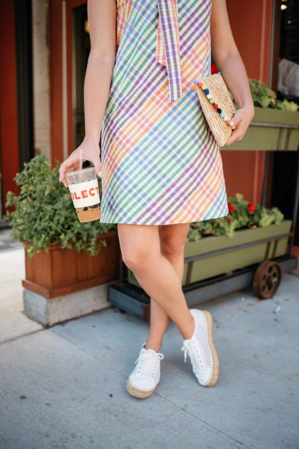 Bows & Sequins wearing a J.Crew dress with white Marc Fisher perforated espadrille sneakers and a pom pom clutch.