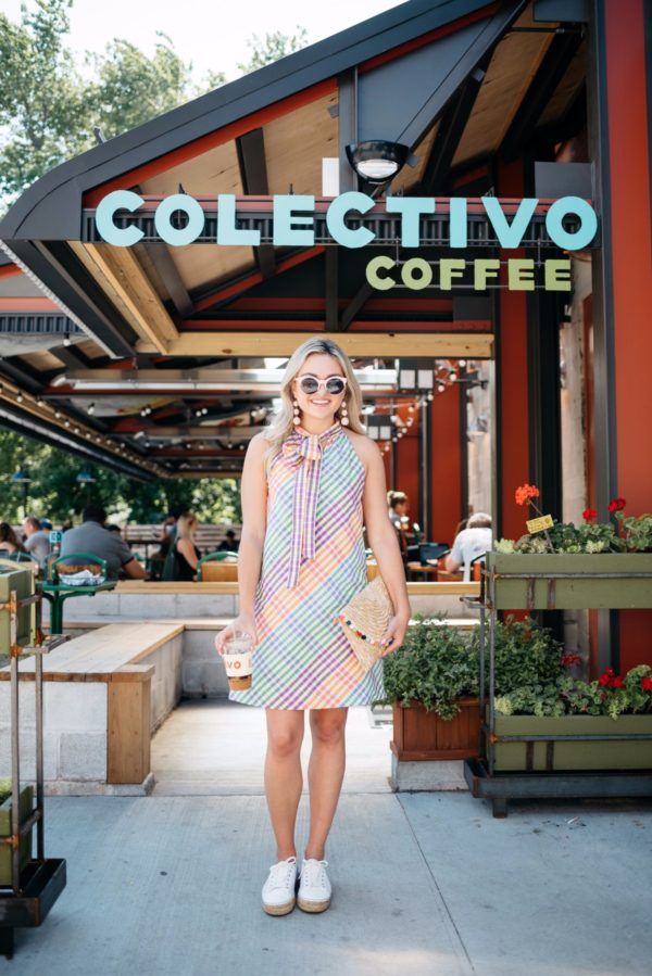 Bows & Sequins wearing a colorful tie neck dress with white espadrille sneakers and a pom pom clutch outside Colectivo Coffee in Chicago.