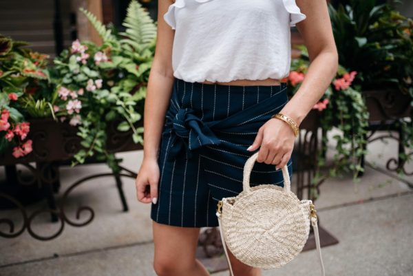 Chicago-based fashion blogger Bows & Sequins wearing a J.O.A. pinstripe tie-front skirt with a Clare V straw tote and Chanel bracelet via Switch.