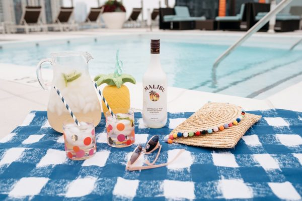 Malibu Coconut Rum summer cocktails on a blue gingham picnic blanket by the pool with Bows & Sequins.