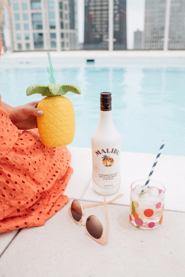 Bows & Sequins holding a pineapple plastic cup by the pool with Malibu Rum.