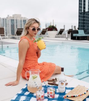 Bows & Sequins wearing an orange eyelet dress on a blue gingham picnic blanket, drinking Malibu Rum coconut cocktails, by the pool.