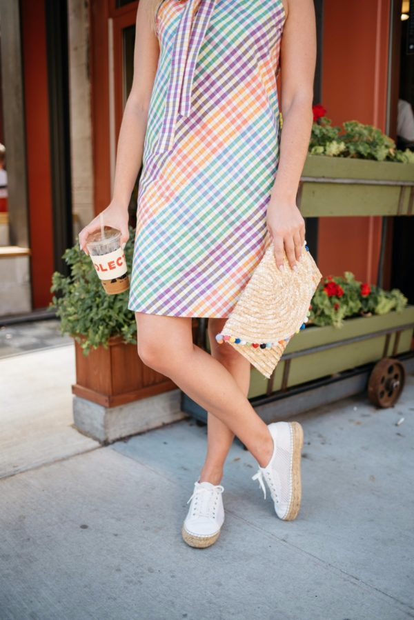 Chicago-based blogger Bows & Sequins wearing a White Elephant Designs pom pom clutch, Marc Fisher espadrilles, and a colorful patterned tie neck dress.