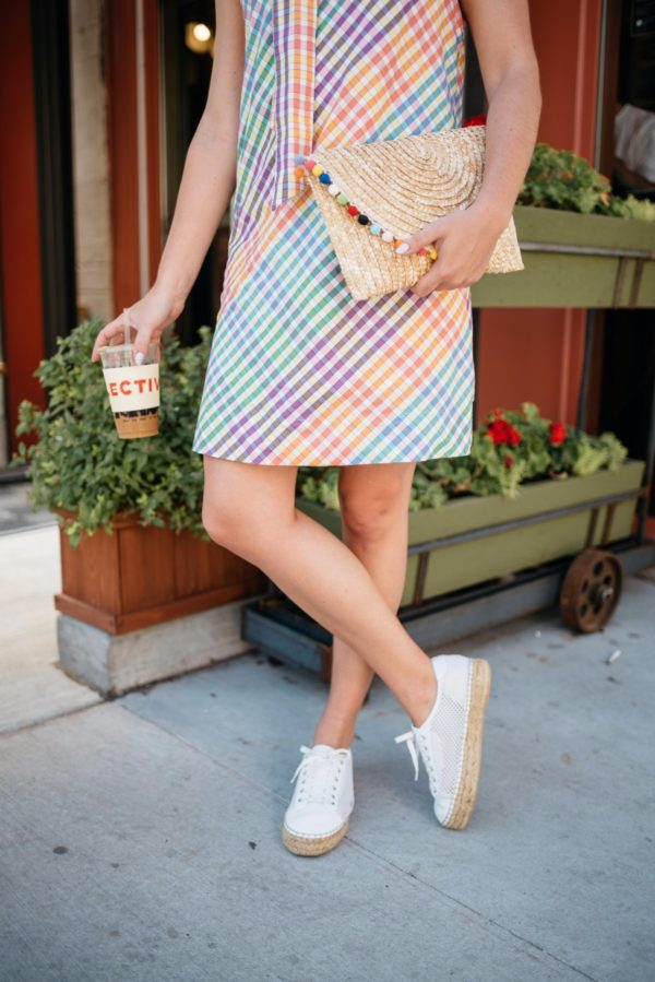Bows & Sequins, a Chicago-based fashion-focused blogger, wearing Marc Fisher espadrille sneakers, pom pom clutch bag, and a J.Crew tie neck dress.