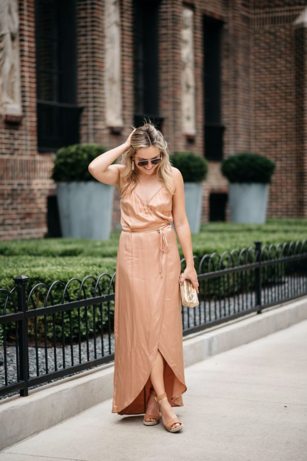 Bows & Sequins styling a Wayf metallic silk dress with gold accessories: a Marc Jacbos pouch, Gucci aviators, and Baublebar rose gold earrings.