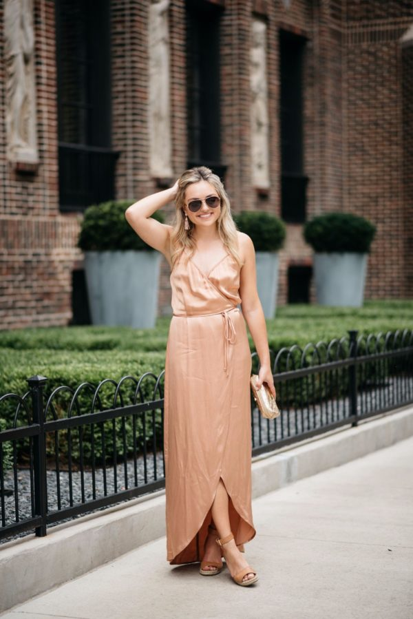 Jessica from Bows & Sequins, a Chicago-based fashion-focused blog, wearing a Wayf silk dress with Gucci aviators, gold pouch, and Vince Camuto wedges.