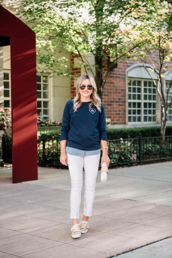 Bows & Sequins styling an affordable fall outfit: Old Navy Love Wins sweatshirt, chambray ruffle top, white denim, and leopard print sneakers.