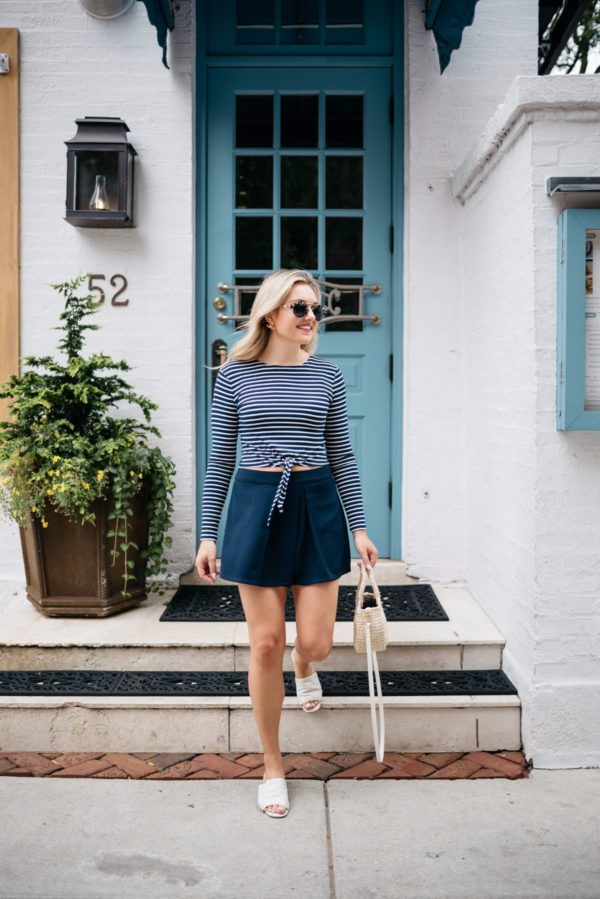 Bows & Sequins wearing a tie-front crop top with Cupcakes & Cashmere pleated shorts, a Clare V straw tote, Illesteva sunglasses, and Kurt Geiger slides.