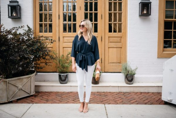 Chicago fashion blogger Bows & Sequins wearing a navy tie-waist blouse with white denim and a wicker clutch.