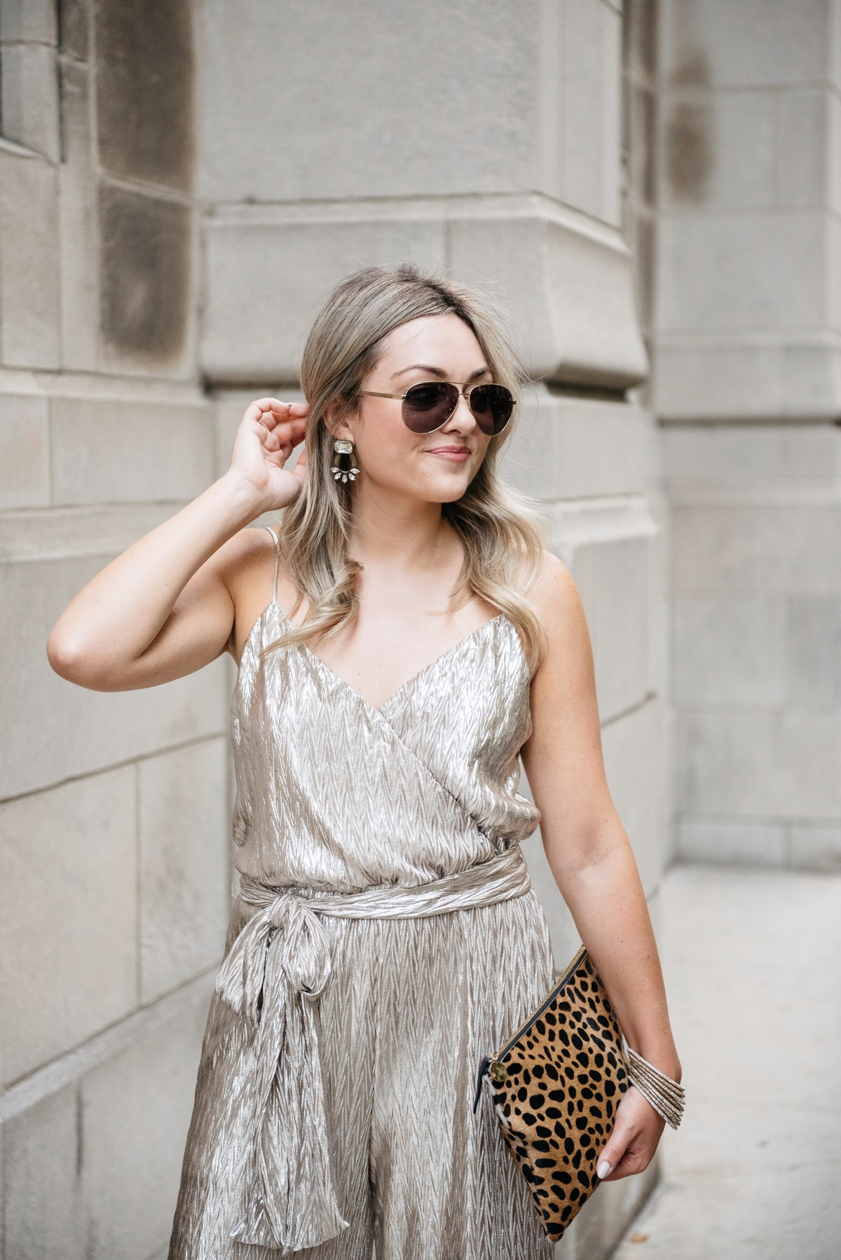 Bows & Sequins styling a metallic gold Plissé jumpsuit from Nordstrom with a Clare V leopard clutch, pavé bangles, Loren Hope earrings, and Gucci sunglasses.