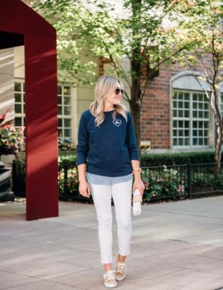 Bows & Sequins wearing an Old Navy Love Wins graphic sweatshirt, white jeans, leopard print sneakers, and a Julie Vos gold cuff with a Vineyard Vines wicker clutch.