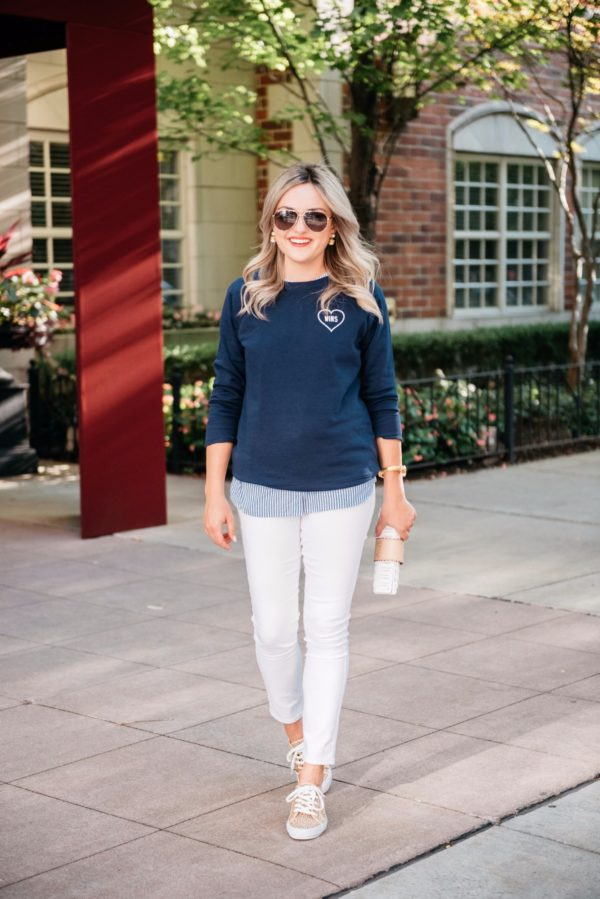 Bows & Sequins styling a Love Wins graphic sweatshirt with white denim, a white rattan clutch, and leopard print sneakers.