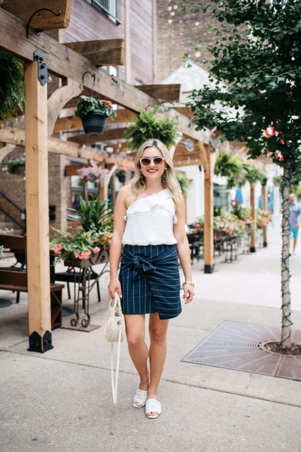 Chicago fashion-focused blogger Bows & Sequins wearing a J.O.A. pinstripe skirt with an ASTR crop top and white leather slides with a Chanel bracelet and Baublebar nautical earrings.
