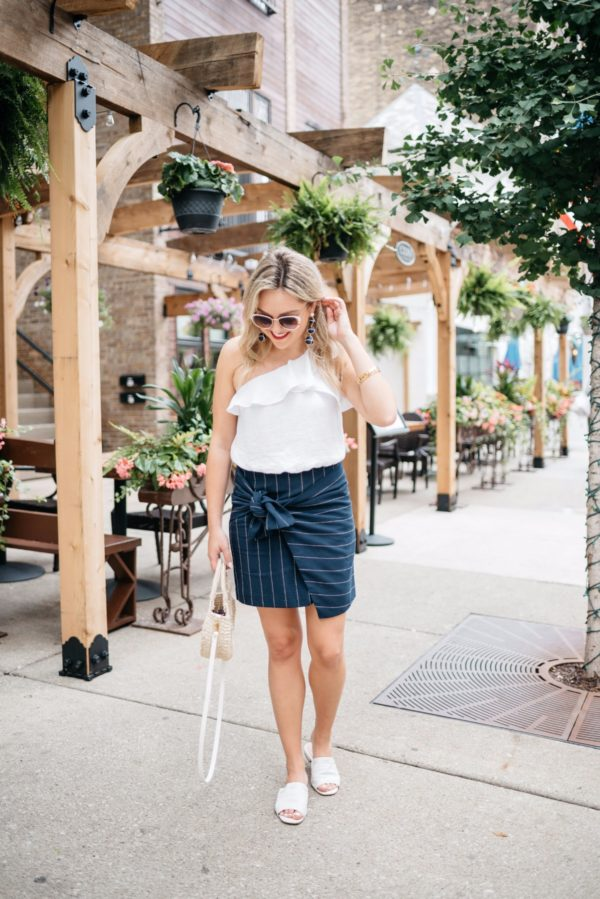 Bows & Sequins wearing a ruffle one-shoulder crop top with a tie-front pinstripe skirt, white leather slides, a straw tote, and white sunglasses.