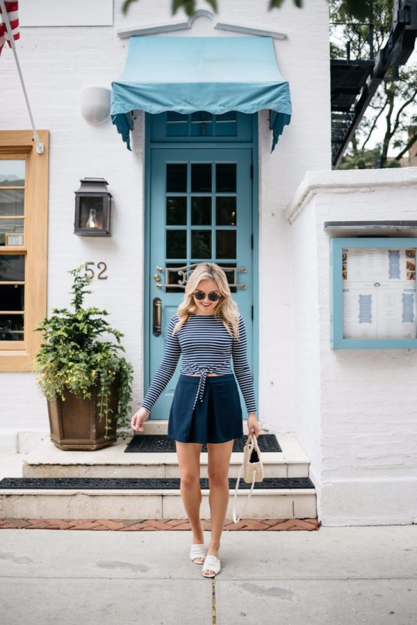 Chicago-based blogger Bows & Sequins wearing a Lovers + Friends tie-front crop top with Cupcakes & Cashmere pleated high-waist shorts, a Clare V straw tote, Illesteva sunglasses, and Kurt Geiger slides.