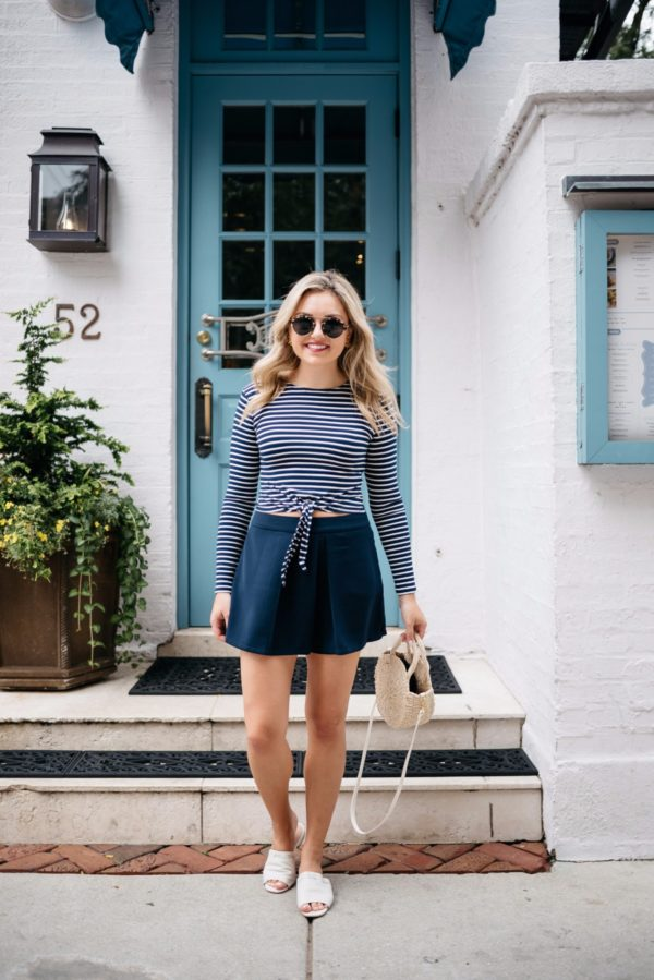 Fashion and lifestyle blogger Bows & Sequins wearing a Lovers + Friends tie-front crop top with Cupcakes & Cashmere pleated high-waist shorts, a Clare V straw tote, Illesteva sunglasses, and Kurt Geiger slides.