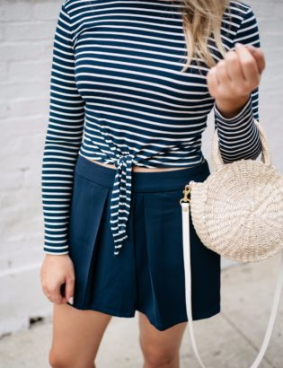 Bows & Sequins wearing a navy striped tie-front crop top with navy pleated shorts and a straw tote.