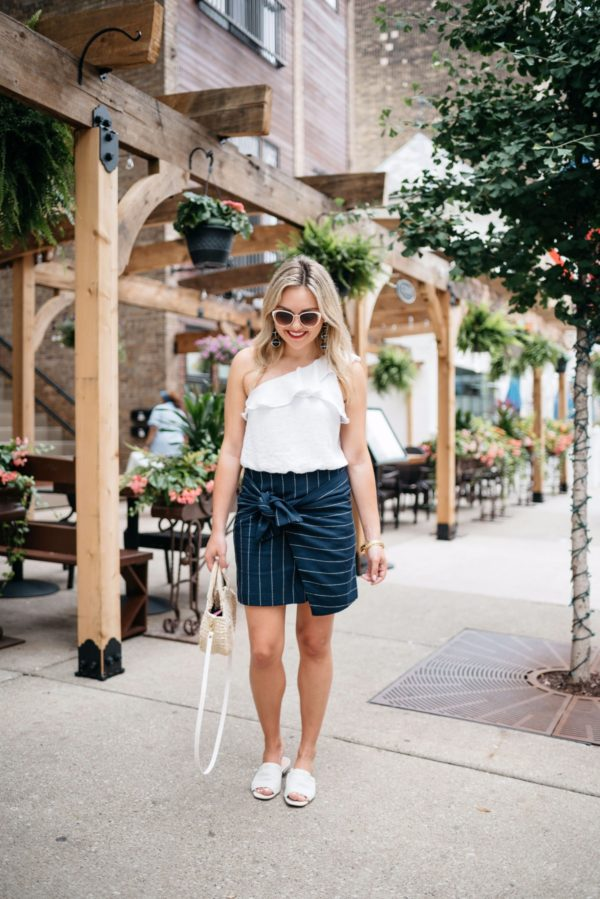 Fashion and lifestyle blogger Bows & Sequins wearing a tie-front navy pinstripe J.O.A. skirt with a one-shoulder crop top, Call It Spring sunglasses, a Clare V straw tote, and Kurt Geiger slides.
