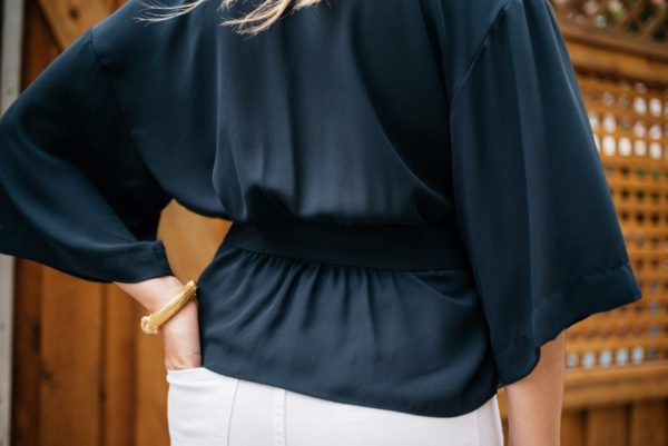 Bows & Sequins wearing a navy Trouve blouse with a Julie Vos gold arm cuff.