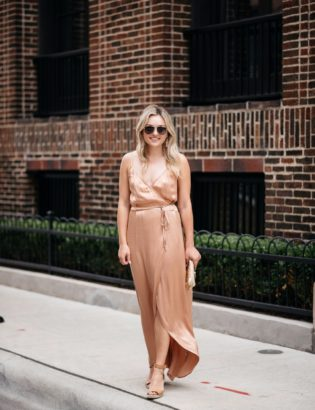 Chicago-based fashion-focused blogger Bows & Sequins wearing gold Gucci aviators, Baublebar rose gold earrings, Charlotte Tilbury nude lipstick, a Wayf metallic silk wrap dress, and Vince Camuto wedges.