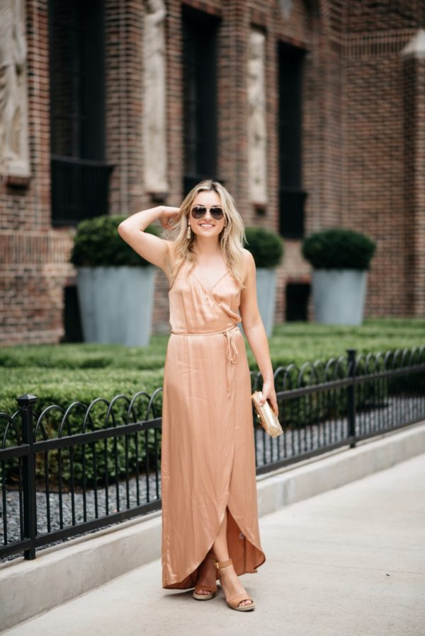 Lifestyle and fashion blogger Bows & Sequins wearing a metallic silk dress with gold aviators, a gold pouch, nude lipstick, and camel wedges.