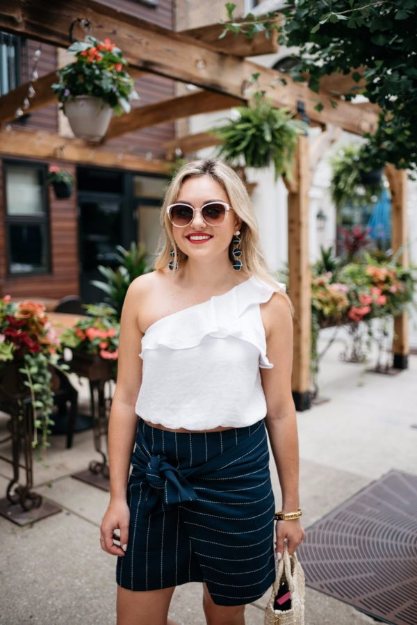 Bows & Sequins wearing Call It Spring sunglasses, an ASTR ruffle one-shoulder crop top, and a front-tie pinstripe skirt.