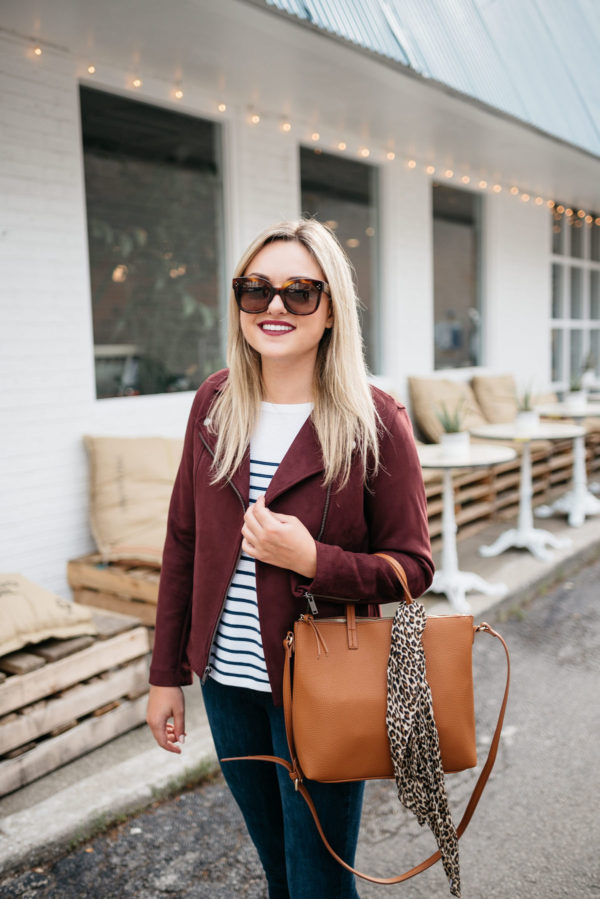 Fashion blogger Bows & Sequins sharing fall outfit inspiration: Celine sunglasses, a burgundy suede moto jacket, striped shirt, and an Old Navy leather bag with a leopard scarf.